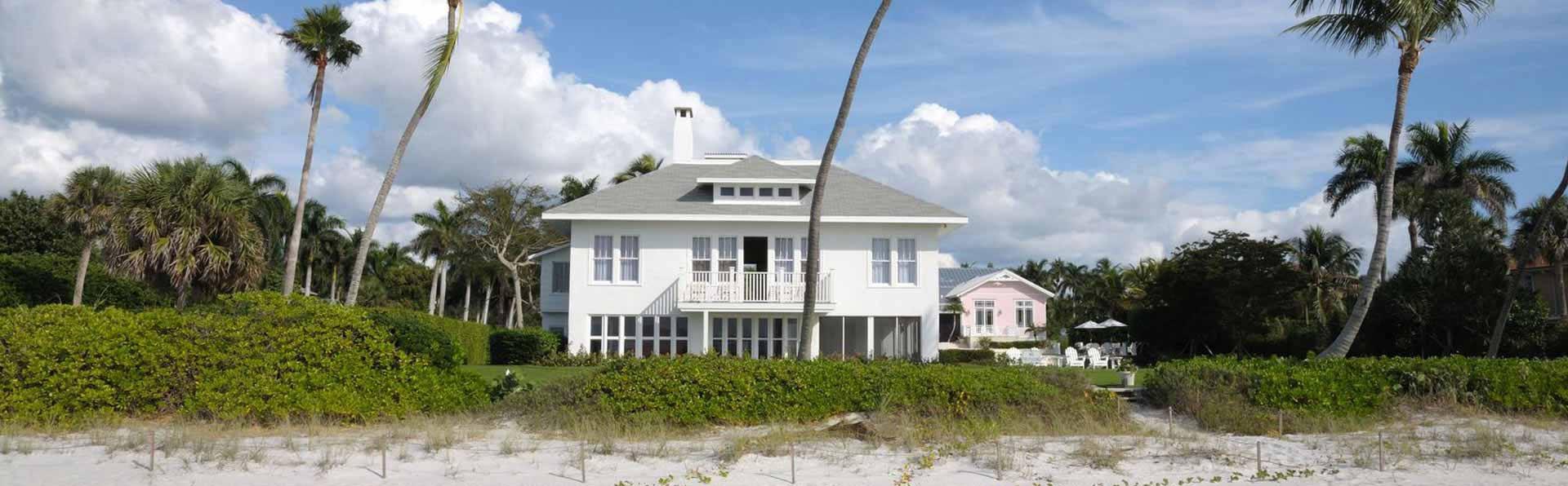 Photo of white 2 story house on beach in Sanibel Island, FL.