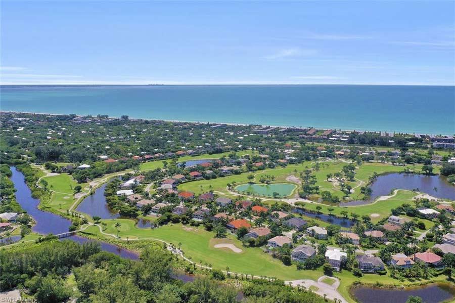 Arial view of Sanibel Island overlooking golf community facing the beach.
